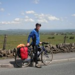 Alan stabding over his bike by the side of the road with green fields in the background and sunshine