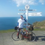 Mark at the finishing post at Lands End with his bike in the sunshine